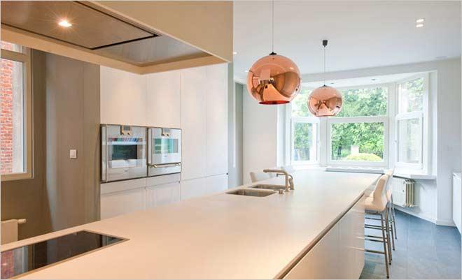 de keuken werd centraal in de ruimte geplaatst waardoor hij zeer veel aandacht krijgt het warm wit kleur van het werkblad werd afgestemd op de fronten van